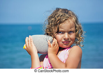 pretty little girl holds in hands pebble on seacoast in ...