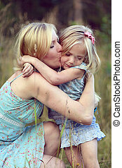 Pretty little girl hugging mom