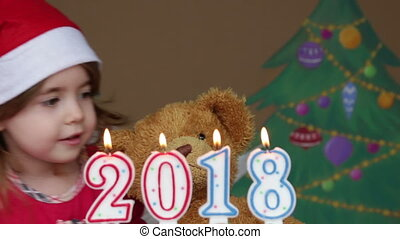 Pretty little girl in a Santa Claus hat blowing out candles. Little girl holding a Christmas teddy bear