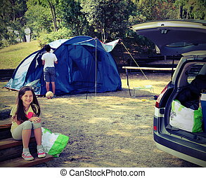 Pretty little girl in camping with the tent and her brother with