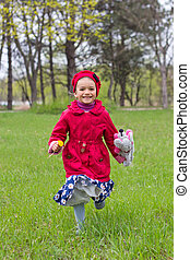 Pretty little girl in red jacket and blue dress with flowers running on green grass in spring