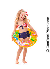 Pretty little girl in red striped bikini, blue bottoms and pink wreath stand stand with colorful rubber ring on the waist