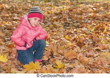 Pretty little girl in the autumn park