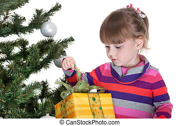Pretty little girl is opening a christmas gift