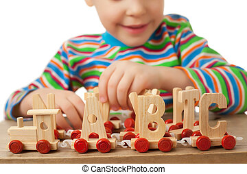pretty little girl is played by toy wooden steam locomotive with cars in form of alphabet letters isolated on white background, steam locomotive close up