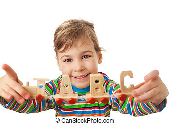pretty little girl keeps in hands toy wooden steam locomotive with cars in form of alphabet letters isolated on white background