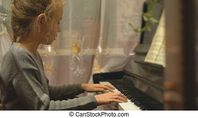 Pretty little girl learns to play the piano.