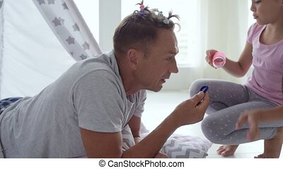 Pretty little girl making a hairstyle for her loving father at home