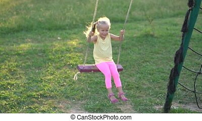 pretty little girl on a swing at the playground