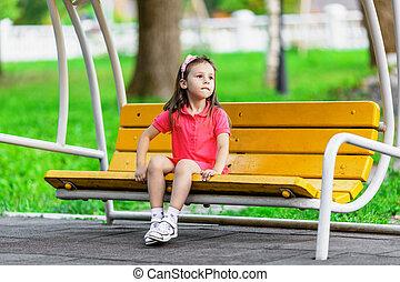 Pretty little girl on swing bench