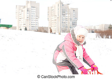 Pretty little girl playing with a sled in snow