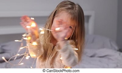 pretty little girl playing with christmas garland. new year, childhood, daughter. Full HD footage.