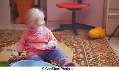 Pretty little girl playing with her toys, sitting on the floor