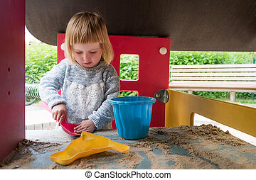 little girl playing with sand