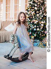 Pretty little girl posing on antique rocking horse against Christmas tree indoors.