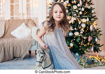 Pretty little girl posing on antique rocking horse against cozy interior with Christmas tree.