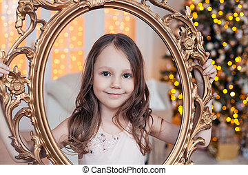Pretty little girl posing with golden vintage frame against Christmas tree indoors.