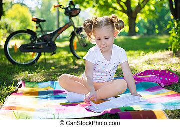 Pretty little girl reading book in green summer park