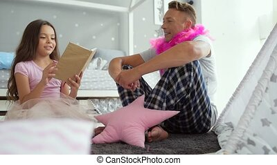 Pretty little girl reading fairy tales with her father -...