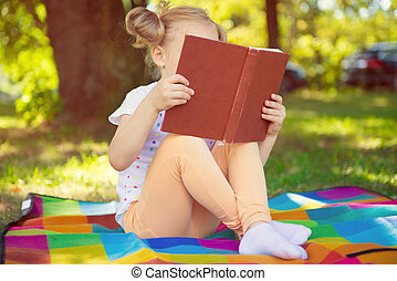 Pretty little girl reading red book in summer park