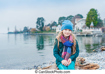 Pretty little girl resting by the lake on a cold cloudy day, wearing hat and scarf, green woolen pullover
