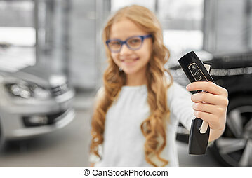 Pretty little girl showing car keys in dealership.
