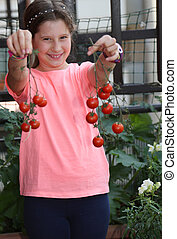 Pretty little girl showing the harvest of tomatoes