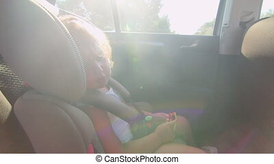 Pretty little girl sings song sitting in child back seat of car on trip