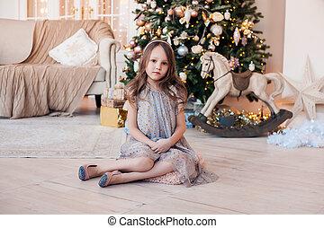 Pretty little girl sitting against Christmas tree indoors.