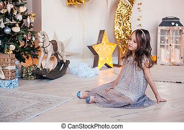 Pretty little girl sitting near Christmas tree indoors.