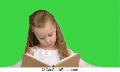 Pretty little girl sitting with book and reading on a Green Screen, Chroma Key