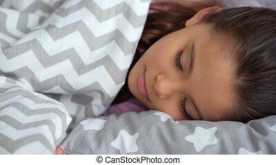 Pretty little girl sleeping in her bed