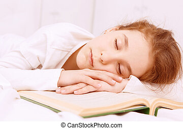 Very interesting book. Cute little red-haired girl sleeping on desk on. opened book