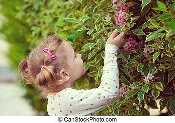 Pretty little girl smell a flower in garden