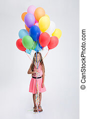 Pretty little girl standing with balloons