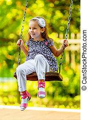 Pretty little girl swinging on seesaw