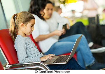 little girl using laptop at airport