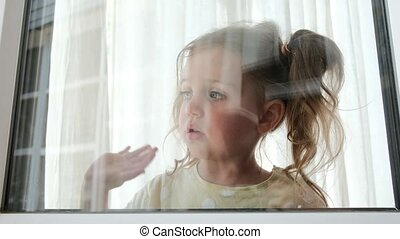 Pretty little girl waves hand looking out of window at home