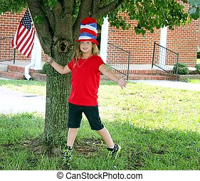 Pretty little girl with 4th of July hat and flag