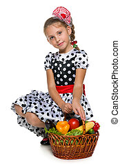 Pretty little girl with a basket of vegetables