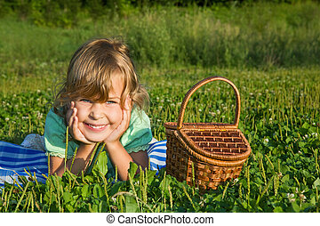 pretty Little Girl with basket on meadow