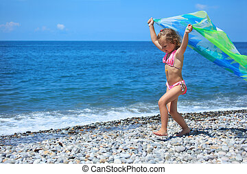 pretty little girl with fabric on stony seacoast, lifted ...