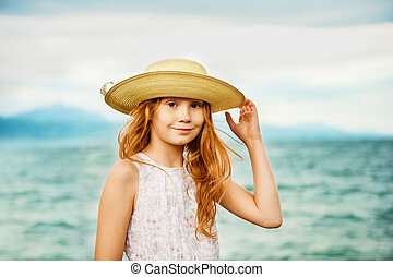 Pretty little girl with long red hair playing by the lake on a very windy day, wearing big hat