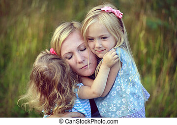 Pretty little girls hugging mom