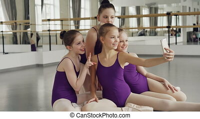 Pretty little girls in bodysuits are taking selfie with smartphone and posing looking at webcam while sitting on studio floor during break between ballet classes.
