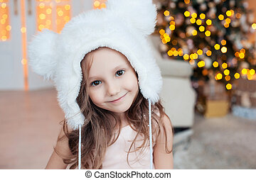 Pretty little smiling girl wearing white fur hat posing against Christmas tree indoors.