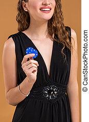 Pretty long hair woman holding chips for gambling. Studio shot. Close-up