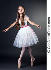 Pretty long-haired ballerina dancing in studio