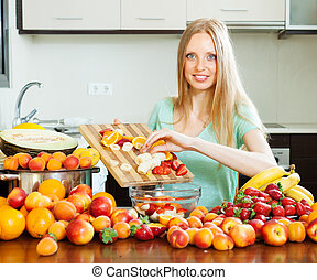 long-haired woman cooking fruit salad