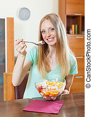 long-haired woman eating fruit salad with yoghurt in home
